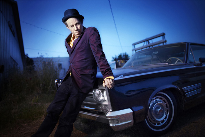 portrait of Tom Waits sitting on a car