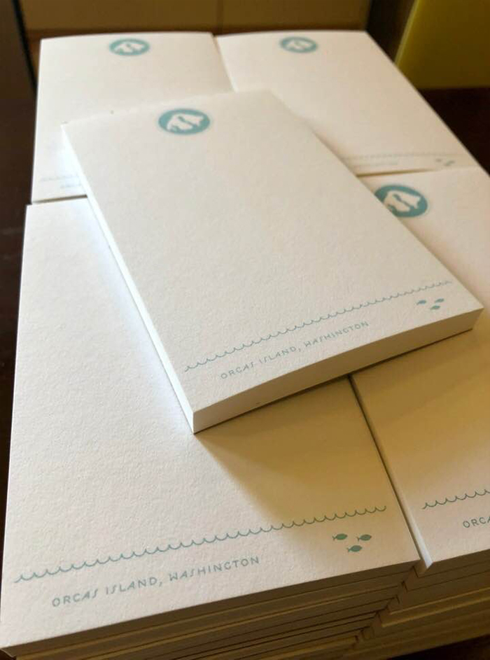 Stack of notepads with map of Orcas on them